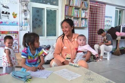 李利娟正在看着孩子做功课。京华时报记者赵思衡摄
